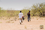 05 MAY 2003 -- SELLS, AZ: People presumed to be undocumented immigrants jump out of a moving car and run into the desert while being pursued by a Tohono O'Odham tribal police officer on AZ Highway 86 west of Sells, AZ, the capital of Tohono OOdham Indian Reservation, May 5, 2003. The officer tried to pull over the car for a traffic violation and the car sped off, after a short pursuit, the driver of the car swerved onto the right of way and the five occupants of the car jumped out and ran into the nearby desert. Such tactics are frequently used by immigrant smugglers trying to evade capture. The Tohono OOdham reservation covers a vast expanse of Southern Arizona and has a 70 mile border with Mexico. In recent years the reservation has been flooded with undocumented immigrants who pass through the reservation on their way north to Phoenix, AZ, and other cities in the US. About 1,500 undocumented immigrants, most from Mexico, cross the reservation, which has more land than the state of Delaware,  every day. According to the tribal government, the tribal police department spends about 60 percent of its resources dealing with crime created by the undocumented immigrants. Many times tribal police officers have to wait hours for the US Border Patrol to respond to calls to pick up undocumented immigrants. PHOTO BY JACK KURTZ