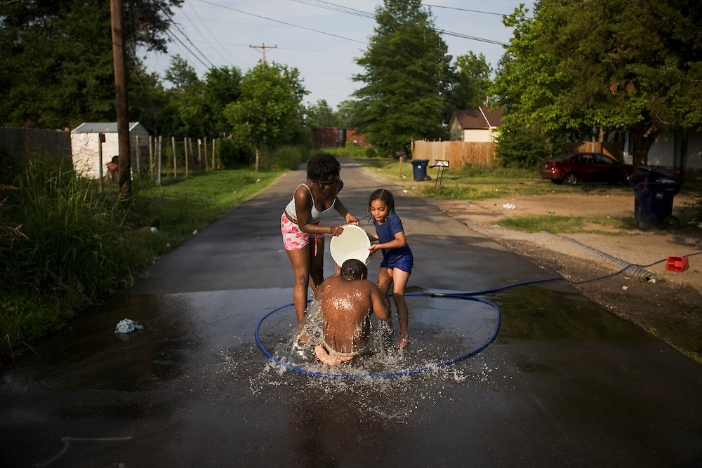 Lacking a public pool in Clarksdale, Miss., a group of children improvise in the middle of 11th st., from left, Kendrika James, 13, Jonathan Lidd, 6, and Niaimani Hopper, 8, on May 23, 2007.<br /> Photo by D.L. Anderson