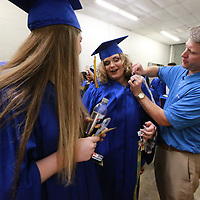 Wesley Hartlein of Herff Jones helps Robin Sutton get her collar attached to her before before finding her spot in line for Friday's graduatin ceremony.