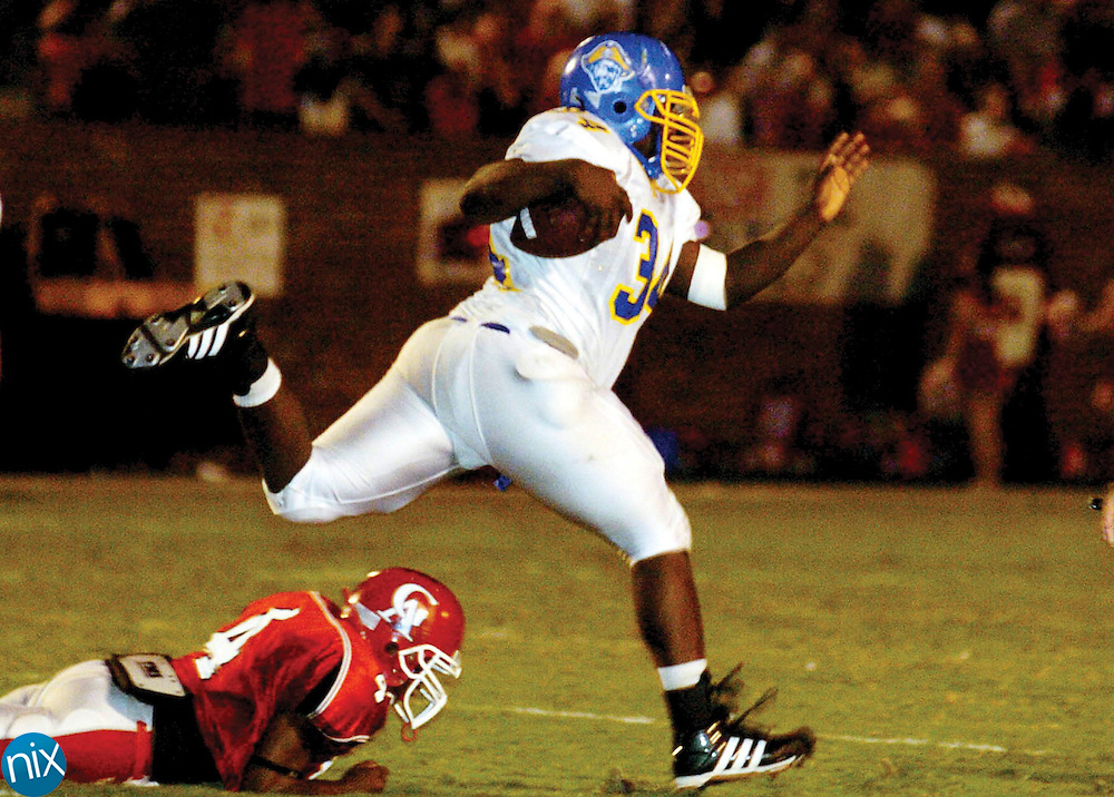 Brunswick High School junior Richard Cash hurdles Glynn Academy's Rex Fulks to pick up a few extra yard during the Pirates' 7-0 win over the Red Terrors in the city championship at Glynn County Stadium Friday night.