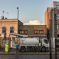 London, UK - 19 September 2014: workmen use suction pumps to clear the street on Wick Road as torrential rains cause floods and travel disruptions in East London