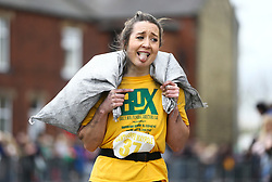 © Licensed to London News Pictures. 17/04/2017. Gawthorpe UK. Competitors take part in the women's race of The World Coal Carrying Championships in the village of Gawthorpe in Yorkshire. Every year Men & women carry huge sacks of coal from the Royal Oak Pub in Ossett 1012 metres to the finish line at the Maypole Green in the village of Gawthorpe. Photo credit: Andrew McCaren/LNP