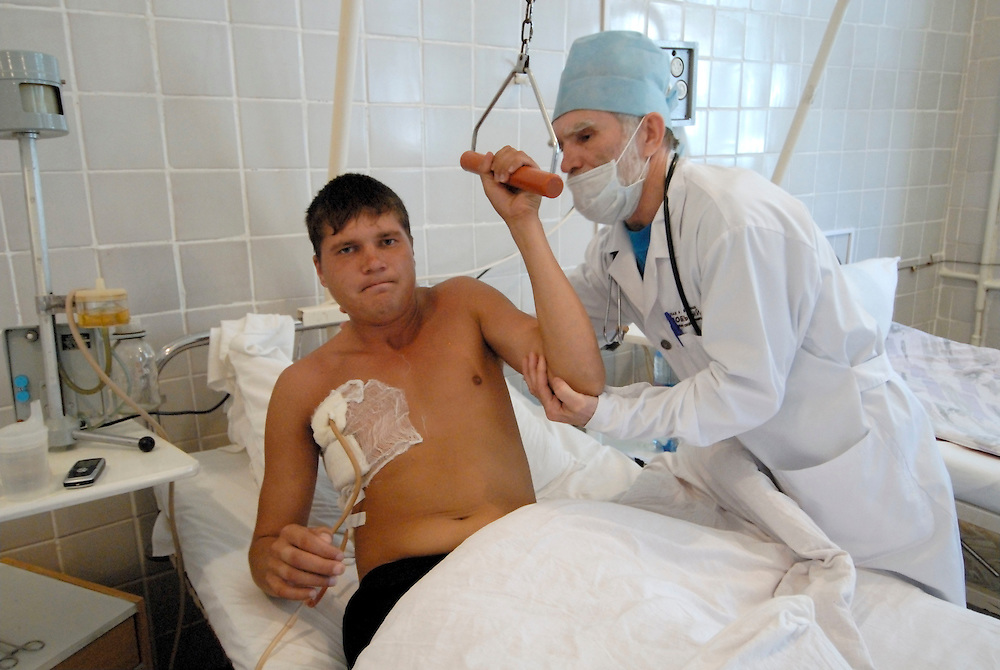 Russia. Tomsk (Siberia). TB Hospital. 23.08.2007. Dr. Anatoly Zadorozhny, helps a TB patient get out of bed, the patient has just been operated on and had 10% of his lung removed..