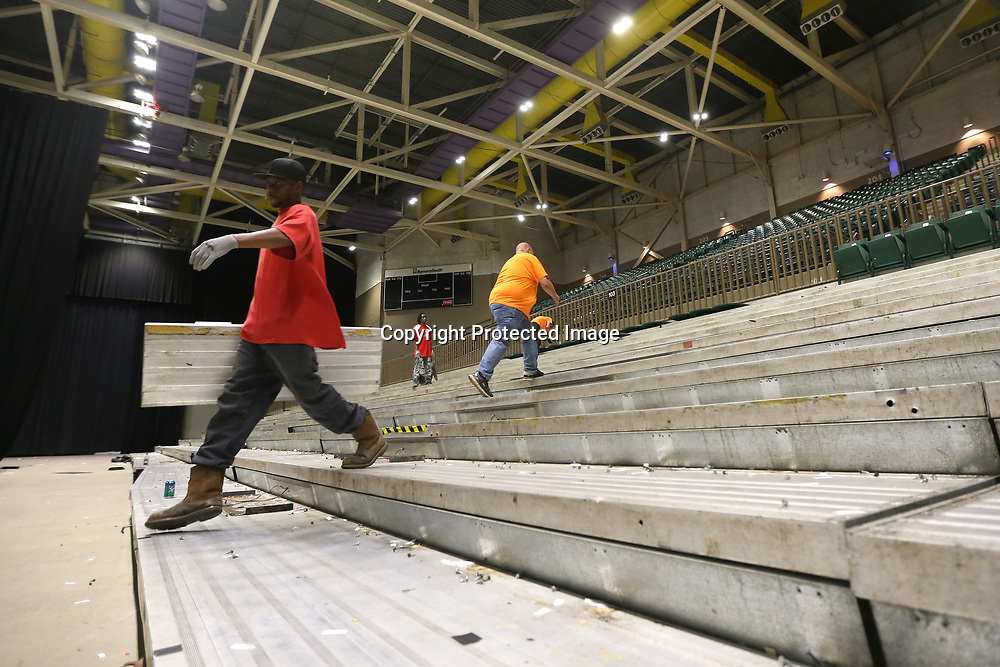 Jermaine Crump carries a set of seats down to the pile as he and a crew work on removing the lower bowl at the BancorpSouth Arena Tuesday morning.