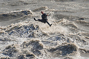 A kite surfer struggles in choppy waves caused by the bore tide on Turnagain Arm at Windy Point outside Anchorage, Alaska.