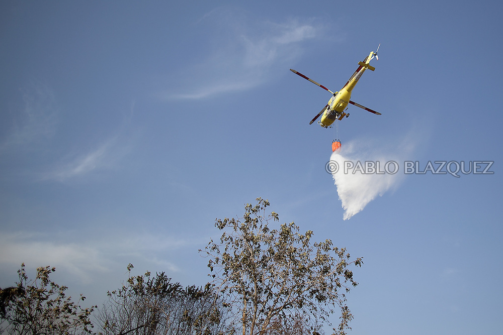 A firefighters helicopter drop water to extinguish a forest fire in San Agustin de Guadalix on August 11, 2012, near Madrid, Spain. During a heat wave dozens of forest fires have appeared in Spain, three of them at National Parks, like Teide, Doñana or Cabañeros, and also thousands of people had to be evacuated at La Gomera and Tenerife, in the Canary Islands.