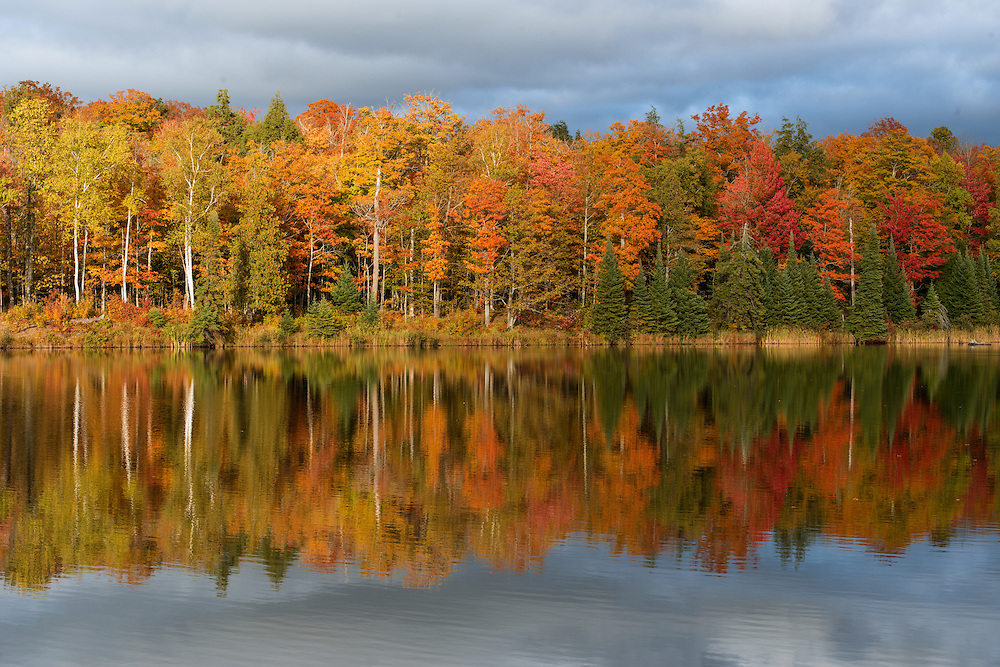 Fall colors reflecting on Lake Plumbago<br /> Michigan's Upper Peninsula