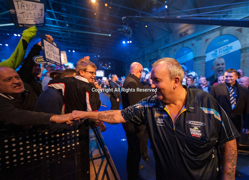 02.01.2014.  London, England.  William Hill PDC World Darts Championship.  Quarter Final Round.  Phil Taylor (2) [ENG] shakes hands with a fan as he makes his way to the stage before his match with Vincent van der Voort (23) [NED]