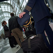 Waiting in line for a departing flight, an airline captain patiently queues with his flight baggage along with passengers. Rather than being on duty and flying the aircraft himself, he is travelling home as a passenger. On many commercial flights, off-duty air crew position as passengers. Airlines plan complicated logistics with cabin and cockpit crew members' duty rosters. This man's four stripes denotes his seniority as a captain who flies right-hand seat, in command of a airliner. In the US, pilots might also have National Guard careers flying jet fighters in times of conflict while off-duty in airline shifts. Picture from the 'Plane Pictures' project, a celebration of aviation aesthetics and flying culture, 100 years after the Wright brothers first 12 seconds/120 feet powered flight at Kitty Hawk,1903. .