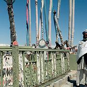 12 April 1976<br /> Kabul. Elaborate iron railing surrounding the tomb area. Caretaker (motawali) standing to right.