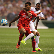 Jordan Ibe, (left), Liverpool, is tackled by Ashley Cole, AS Roma, during the Liverpool Vs AS Roma friendly pre season football match at Fenway Park, Boston. USA. 23rd July 2014. Photo Tim Clayton