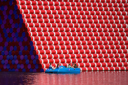 © Licensed to London News Pictures. 01/08/2018. LONDON, UK.  People in a pedal boat pass by The London Mastaba on The Serpentine during the warm weather in Hyde Park.  Temperatures are forecast to increase back to the 30s in time for the weekend.  The sculpture by the artist Christo comprises 7,506 horizontally-stacked coloured barrels secured on a floating platform.  The geometric form takes inspiration from ancient mastabas from Mesopotamia and will be on display until 21 September 2018  Photo credit: Stephen Chung/LNP