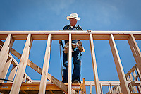 JEROME A. POLLOS/Press..Bob McDonald, from Diana, Texas, aligns lumber for framing Monday while working on the construction of the Grace Baptist Church in Post Falls.