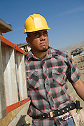 Construction worker carrying step ladder on construction site