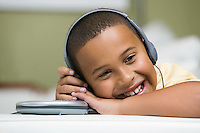 Boy on sofa Listening to portable CD player close up