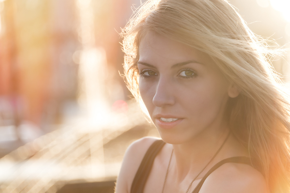 Pensive attractive young blond woman looking at the camera in a golden glowing light