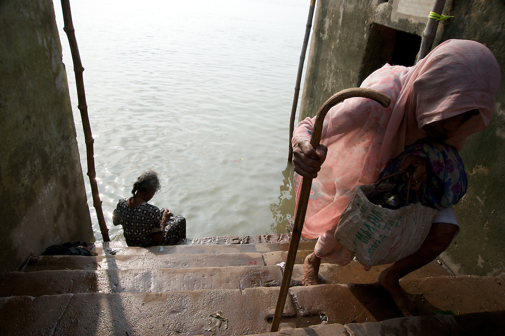 An elderly woman with cane in hand returns towards her home after her morning bath in the Ganges River, Varanasi, India.