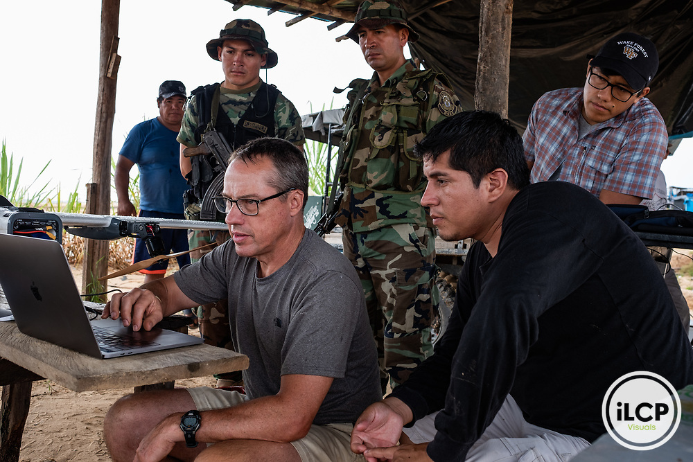 Wake Forest University biology professor, Dr. Miles Silman shows Peruvian National Police Special Forces members at the Mega 12 base aerial images from CINCIA's fixed wing drone while Drone and GIS Coordinator Jorge Caballero Espejo (checked shirt) looks on. Following Peru's February 2019 militarized crackdown on illegal and unofficial alluvial gold mining in the La Pampa region of Madre de Dios, Wake Forest University's Puerto Maldonado-based Centro de Innovación Científica Amazonia (CINCIA), a leading research institution for the development of technological innovation for biological conservation and environmental restoration in the Peruvian Amazon, is applying years of scientific research and technical experience related to understanding mercury contamination and managing Amazonian ecosystems. What they learn will help guide urgent remediation, restoration, and reforestation efforts that can also serve as models for how we address the tropic's most dramatically devastated landscapes around the world. La Pampa, Madre de Dios, Peru.