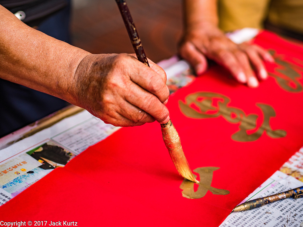 "18 JANUARY 2017 - BANGKOK, THAILAND: A traditional Chinese calligrapher draws New Years greetings that he sells in Bangkok's Chinatown district, before the celebration of the Lunar New Year. Chinese New Year, also called Lunar New Year or Tet (in Vietnamese communities) starts Saturday, 28 January. The coming year will be the ""Year of the Rooster."" Thailand has the largest overseas Chinese population in the world; about 14 percent of Thais are of Chinese ancestry and some Chinese holidays, especially Chinese New Year, are widely celebrated in Thailand.       PHOTO BY JACK KURTZ"