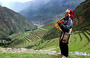 Indigenous Quechua man in colourful clothes plays the flute, Cusco, Peru