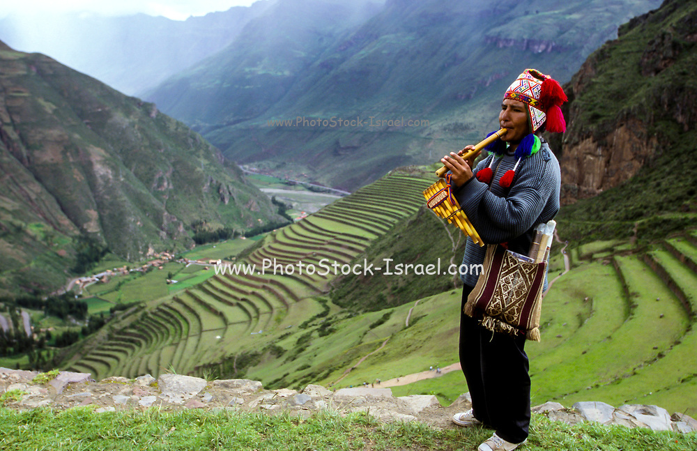Indigenous Quechua man in colourful clothes plays the flute, Cusco, Peru