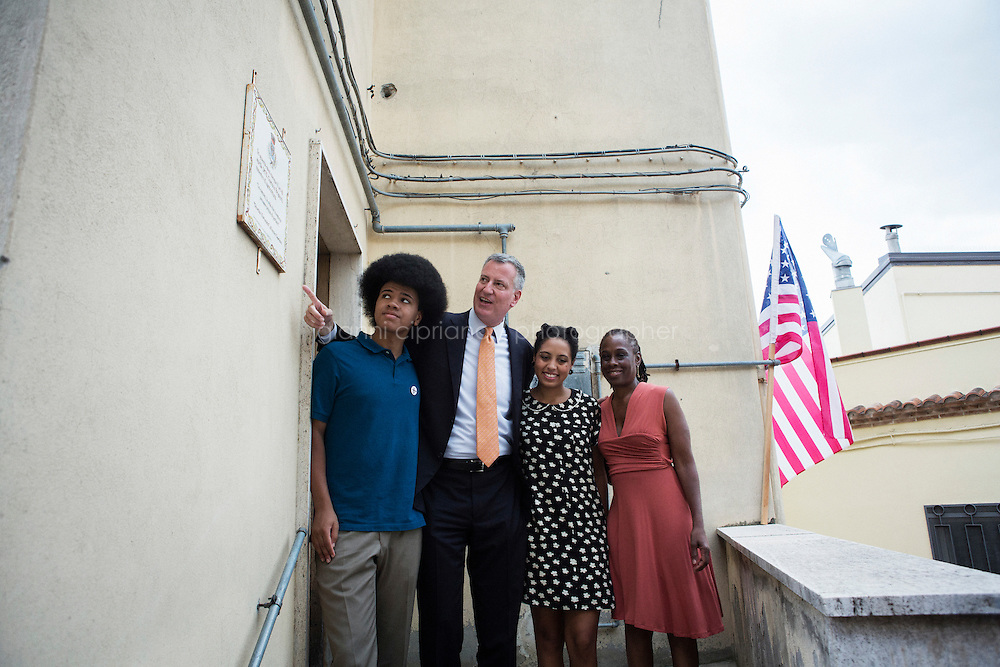 GRASSANO, ITALY - 24 JULY 2014: Mayor of New York Bill de Blasio shows his family a commemorative for Gaetano Briganti for being a master of agriculture, here at the entrance of the house where Mr Briganti grew up with his sister Anna Briganti (Mayor of New York Bil de Blasio's grandmother)  in Grassano,<br /> Mr de Blasio's ancestral home town in Italy, on July 24th 2014.<br /> <br /> A commemorative plaque for Gaetano Briganti for being a master of agriculture, is here at the entrance of the house where he grew up with his sister Anna Briganti (Mayor of New York Bil de Blasio's grandmother)  in Grassano,<br /> <br /> New York City Mayor Bill de Blasio arrived in Italy with his family Sunday morning for an 8-day summer vacation that includes meetings with government officials and sightseeing in his ancestral homeland.