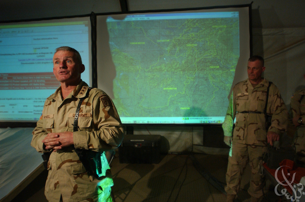 "U.S. Army General Dan McNeill, Coalition Joint Task Force (CJTF) 180 commander (l), speaks to the news media inside the recently constructed CJTF-180 Joint Operations Center May 29, 2002 at Bagram airbase in Afghanistan. As of May 31, 2002, the high-tech operations center will control all U.S. and coalition forces in the Afghan theater of operation via a secure high speed ""secret"" Internet network under McNeill's command."