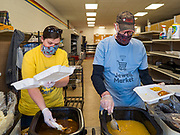 """26 APRIL 2020 - JEWELL, IOWA: CARA ZANKER, and KENN OUTZEN, members of the group trying to reopen a grocery store in Jewell, plate up roast pork dinners for grab and go meals. Jewell, a small community in central Iowa, became a food desert when the only grocery store in town closed in 2019. It served four communities within a 20 mile radius of Jewell. Some of the town's residents are trying to reopen the store, they are selling shares to form a co-op, and they hold regular fund raisers. Sunday, they served 550 """"grab and go"""" pork roast dinners. They charged a free will donation for the dinners. Despite the state wide restriction on large gatherings because of the COVID-19 pandemic, the event drew hundreds of people, who stayed in their cars while volunteers wearing masks collected money and brought food out to them. Organizers say they've raised about $180,000 of their $225,000 goal and they hope to open the new grocery store before summer.           PHOTO BY JACK KURTZ"""