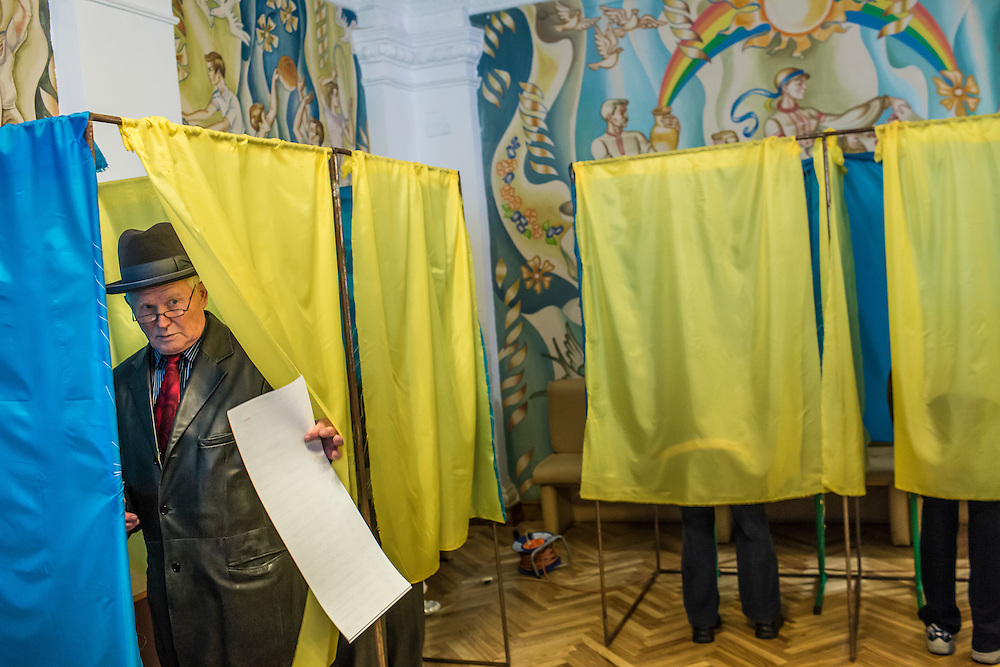 KIEV, UKRAINE - OCTOBER 26: A man emerges from a voting booth after filling in his ballot for parliamentary elections on October 26, 2014 in Kiev, Ukraine. Although a low turnout is expected in the east of the country amid continued fighting between Ukrainian forces and pro-Russian separatists, Ukraine is expected to elect a pro-Western parliament in a further move away from Russian influence. (Photo by Brendan Hoffman/Getty Images) *** Local Caption ***