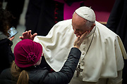 A woman caresses Pope Francis's face at the Paul VI audience hall on December 13, 2017 at the Vatican.
