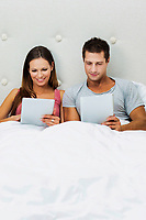 Portrait of attractive couple using digital tablet on bed