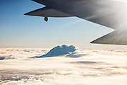 The wing of a 737-400 jetliner frames Mount Rainier, the tallest mountain in Washington state, which rises over a solid bank of clouds.