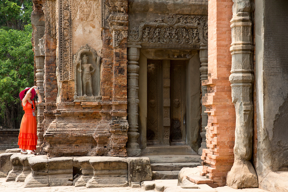 A woman in a red dress and bright pink hat stands to photograph the central tower of the ancient Preah Ko temple, Roluos, Svay Chek District, Banteay Meanchey Province, Cambodia, South East Asia.  The tower is made of brick and perches on a sandstone platform. This tower is dedicated to Jayavarman II, the founder of the Khmer empire.  (photo by Andrew Aitchison / In pictures via Getty Images)