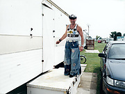 Man standing outside of trailer front door smiling.
