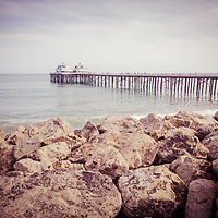 Malibu Pier picture in Malibu California with breakwall rocks. Photo has a vintage retro tone.