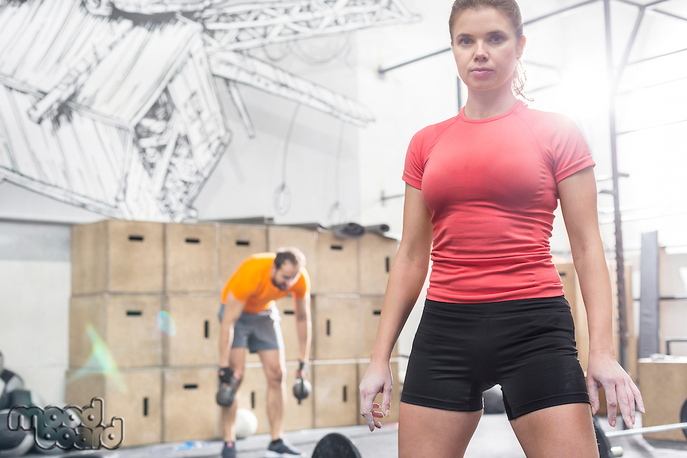 Portrait of confident woman standing in crossfit gym