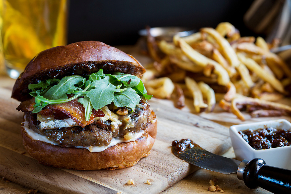 Juicy bacon hamburger on wooden cutting board with french fries and beer.  Served with fig jam.