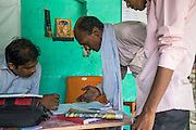 Jeevika Field Associate Jagganath Prasad (centre), reports after returning from the local markets with a top up of vegetables that is needed by the collection centre to be sold to their buyers in Muzaffarpur, Bihar, India on October 27th, 2016. Non-profit organisation Technoserve works with women vegetable farmers in Muzaffarpur, providing technical support in forward linkage, streamlining their business models and linking them directly to an international market through Electronic Trading Platforms. Photograph by Suzanne Lee for Technoserve