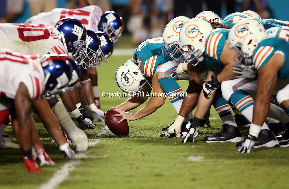 The Miami Dolphins offensive line gets set for the snap at the line of scrimmage opposite the New York Giants defensive line during the NFL week 14 regular season football game against the New York Giants on Monday, Dec. 14, 2015 in Miami Gardens, Fla. The Giants won the game 31-24. (©Paul Anthony Spinelli)