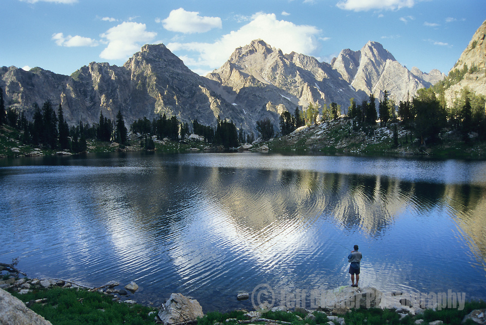 A solitary man fly fishing at a mountain lake in Grand Teton National Park, Jackson Hole, Wyoming.