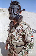 An Egyptian soldier wears a gas mask during a chemical weapons drill along the sand berm frontline border wall separating Kuwait from Saudi Arabia February 8, 1991 in Ar Ruqi, Saudi Arabia.