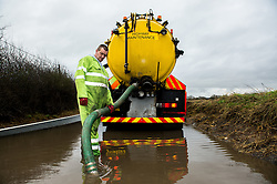 Workmen trying to pump water away from a flooded lane after heavy rains. UK February 2013