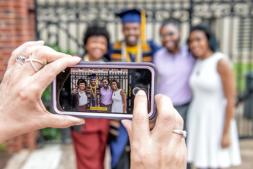 A graduating Howard student with his family, posing for a family photo.