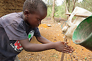 A boy washes his hands at a pedal-activated hand washing station outside a home latrine in the village of Kawejah, Grand Cape Mount county, Liberia on Friday April 6, 2012. As part of the UNICEF sponsored CLTS programme, communities learn to put in practice good hygiene and sanitation practices.