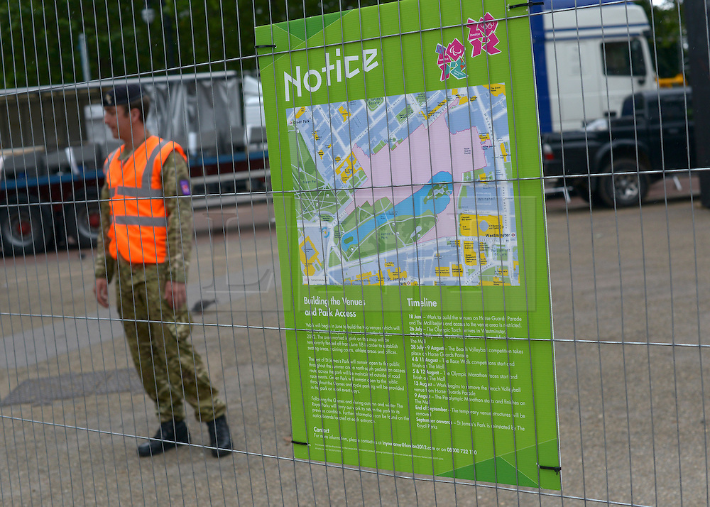 © Licensed to London News Pictures. 18/07/2012. Westminster, UK A soldier next to an Olympic sign at St james Park. Soldiers, police and security contractors perform security checks around Olympic sites in Westminster today, 18th July 2012. Photo credit : Stephen Simpson/LNP
