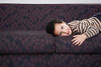 Boy (5-6) lying on sofa portrait