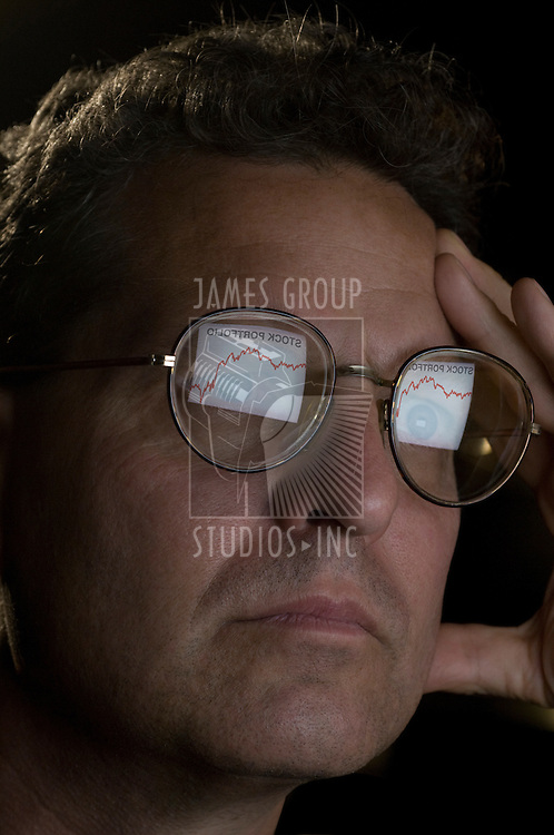 Close-up of a man with the reflection of his computer screen in his glasses showing a declining stock portfolio