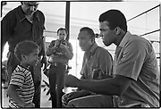 Muhammad Ali - 5th St Gym/Miami Beach, FL      Tri-X     September 1970<br /> training/workout prior to fighting Jerry Quarry in Atlanta (Oct 1970);<br /> playing with Craig Armbrister (3-1/2 yrs old), his godchild; Ali's father, Cassius Marcellus Clay, Sr, sits to his right