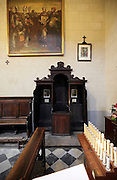 confessional near an altar with electronic candles Italy