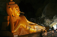 """Reclining Buddha at Wat Tham Suwankuha, a 100-year-old temple hidden inside a cave housing various images of Buddha, including this reclining one.  Wat Tham Suwankuha is also known as Wat Tam, Wat Tham and """"the monkey temple"""" fpr its large population of macaque monkeys."""